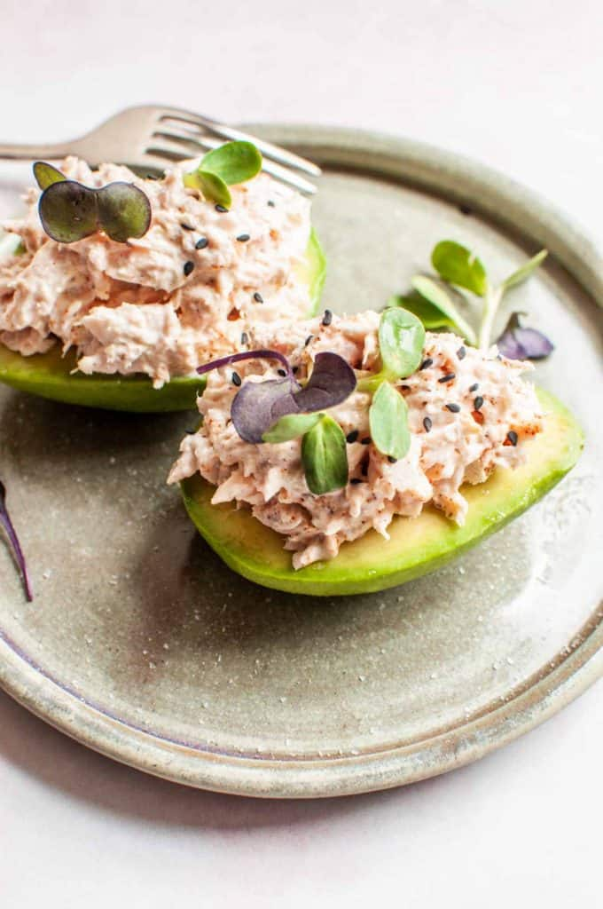 side shot of two tuna stuffed avocados on a plate