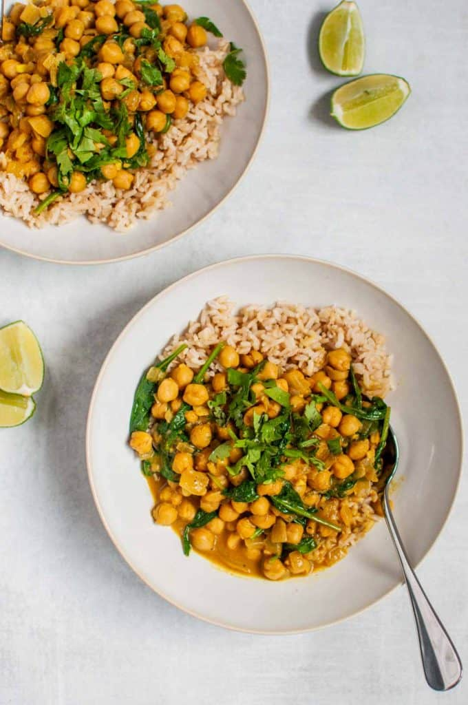 chickpea curry in two bowls with brown rice