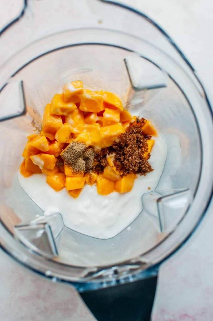 overhead shot of mango lassi ingredients in a blender