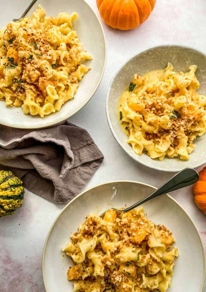 three bowls of butternut squash pasta with mini gourds next to them
