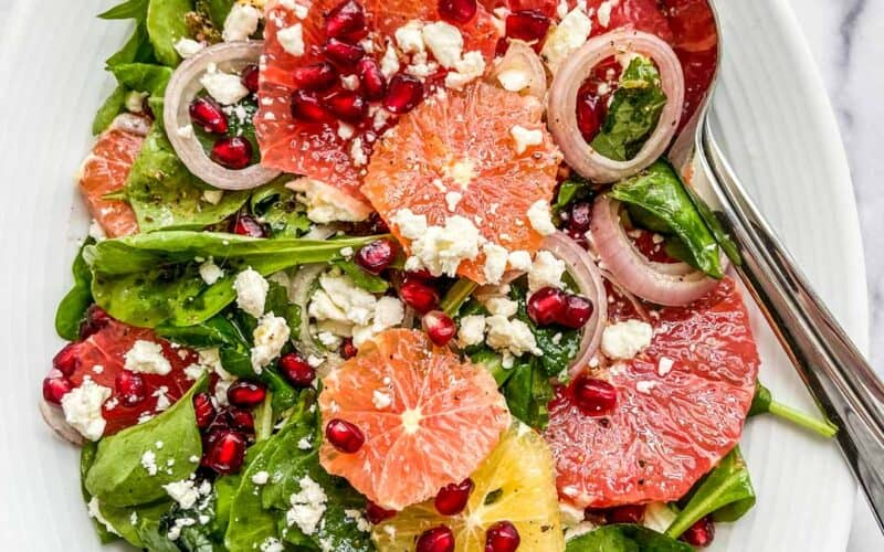 citrus pomegranate salad on a large serving dish with serving spoon