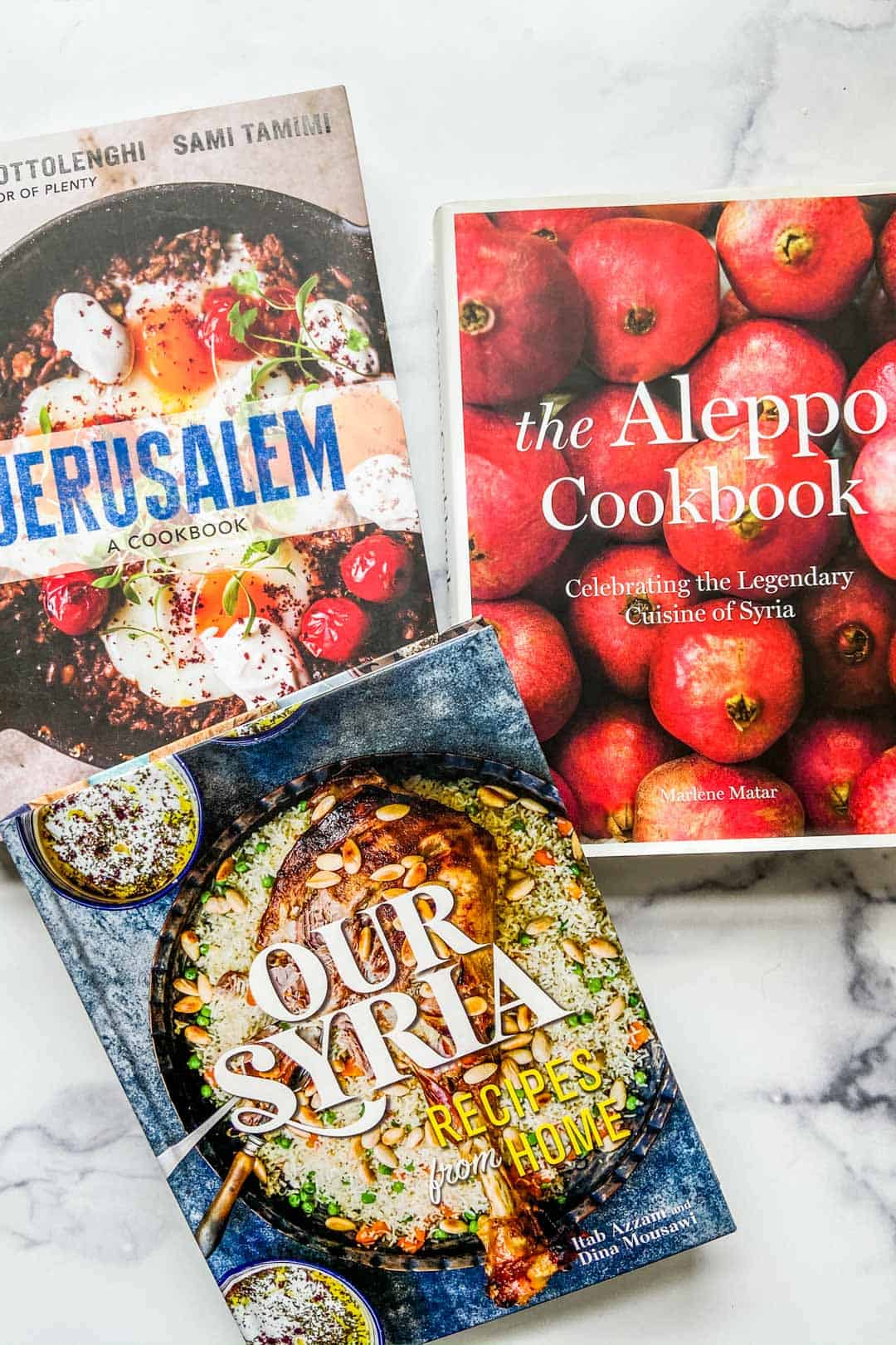 Middle Eastern cookbooks on a marble background.