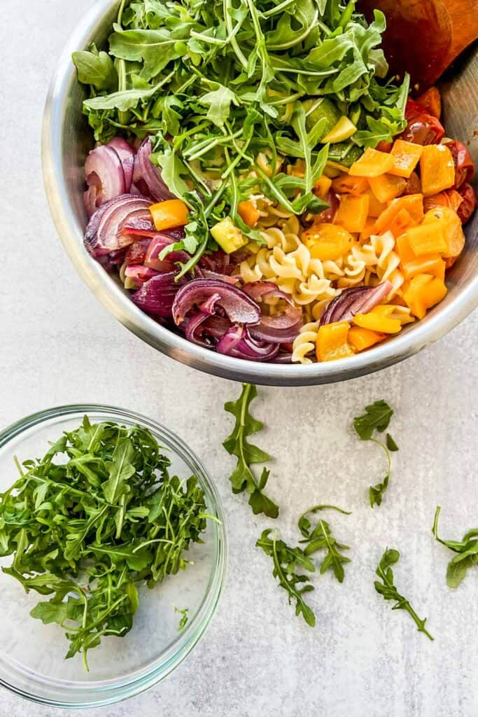 roasted veggie pasta in a large mixing bowl with a small side bowl of arugula