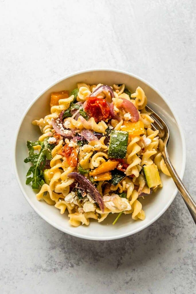 roasted veggie pasta in a bowl with a fork