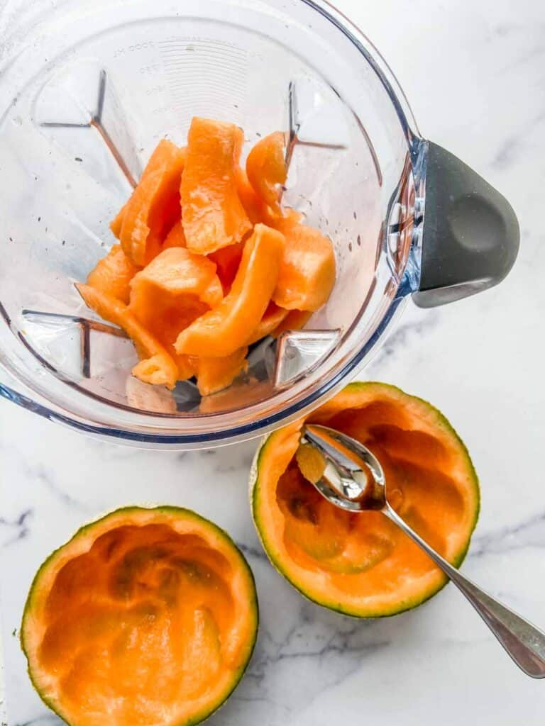 Cantaloupe melons scooped out into a blender.
