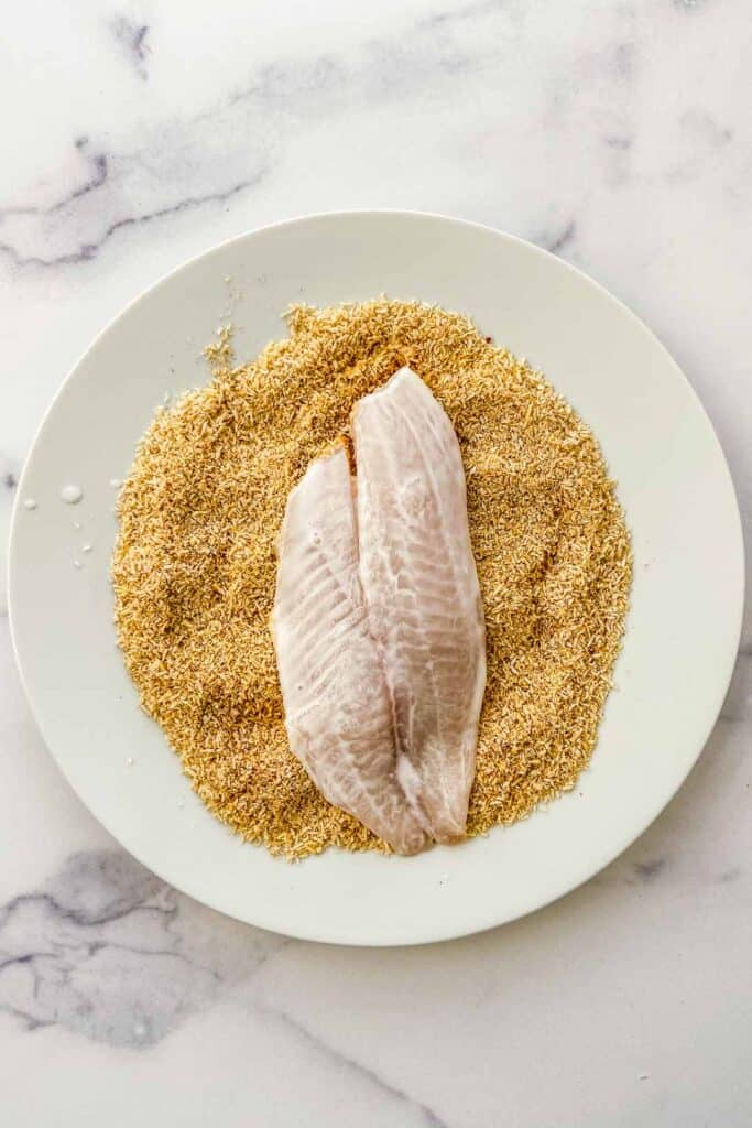 tilapia being dredged in coconut flakes and spices