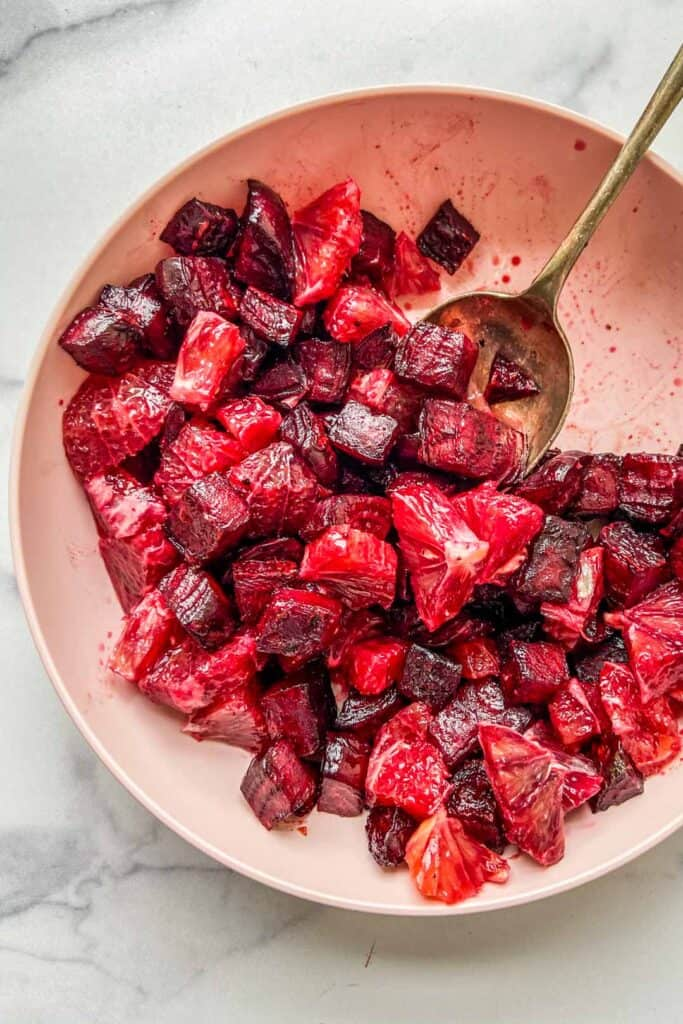 roasted beets and blood oranges in a pink serving bowl