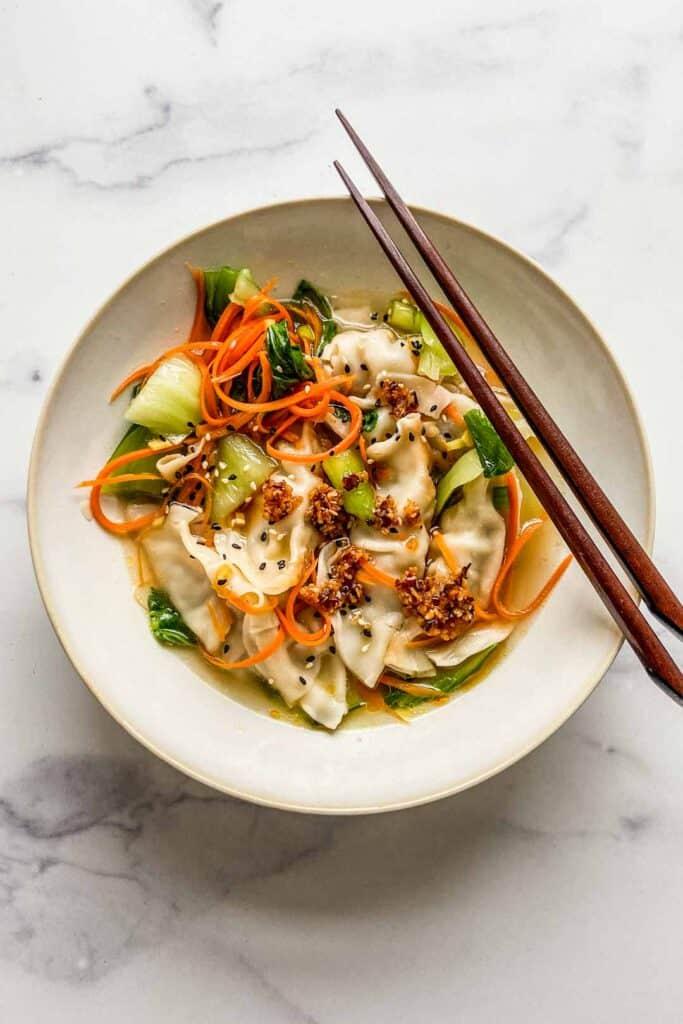 gyoza soup in a bowl with chopsticks