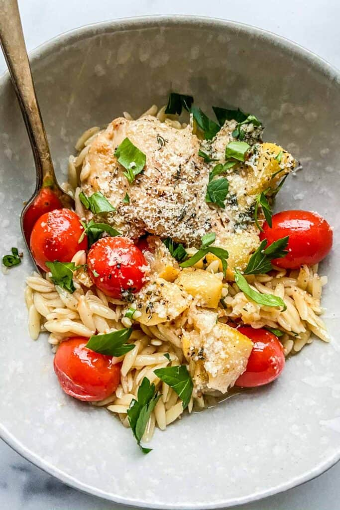 lemon chicken with orzo in a bowl with a fork.