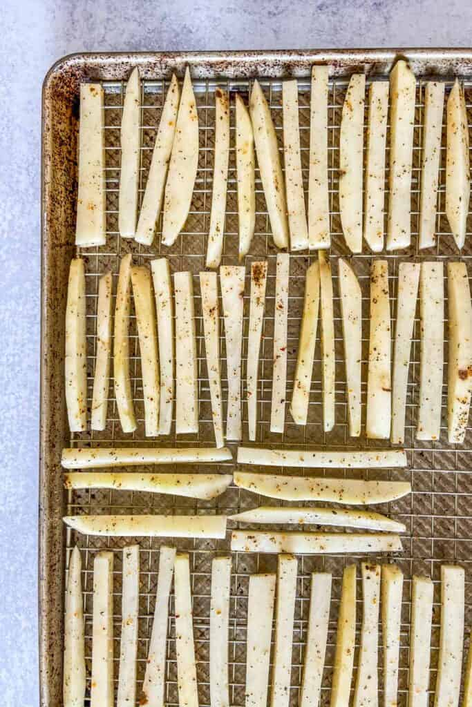 Uncooked fries on a baking sheet.