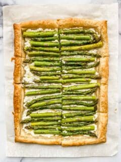 An asparagus tart on a piece of parchment paper.