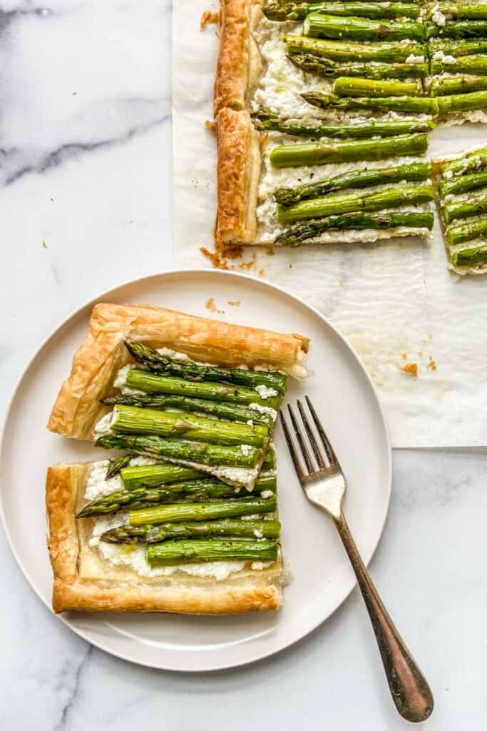 Two pieces of an asparagus tart on a white plate with a fork.