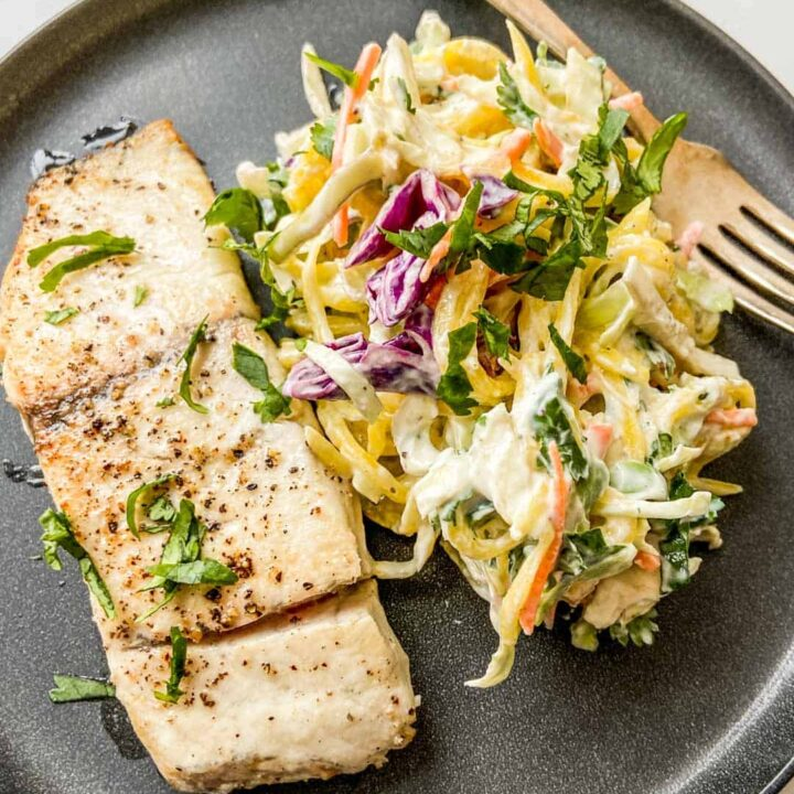 Closeup shot of a barramundi fillet next to mango slaw on a black plate with a fork.