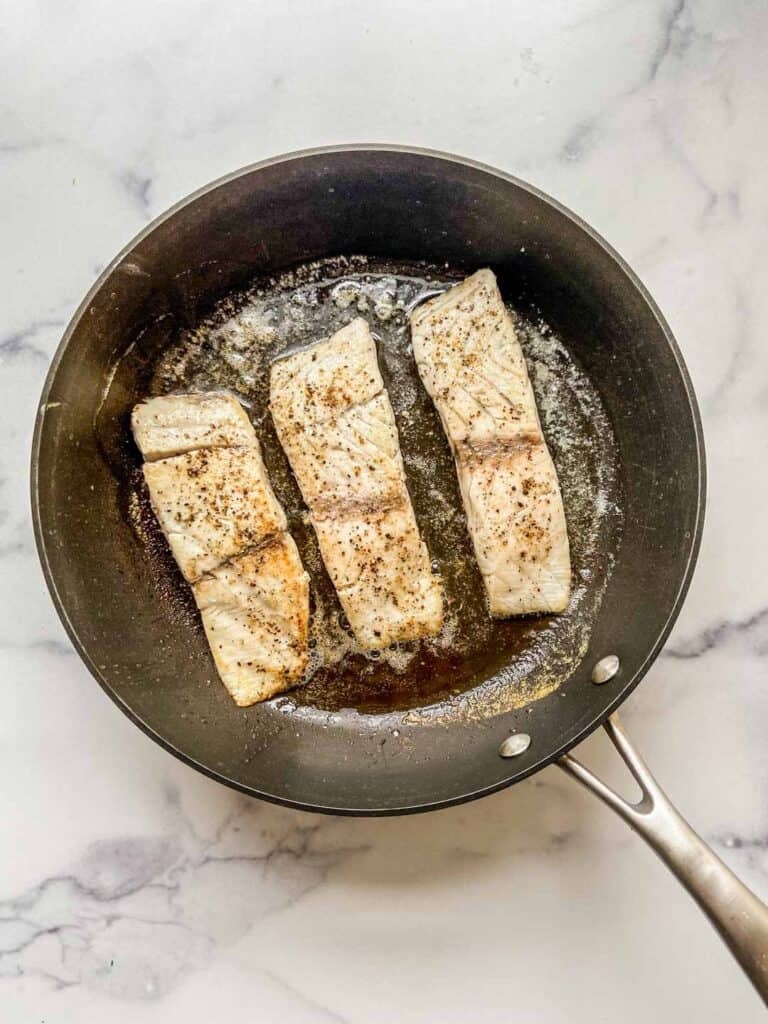 Three barramundi fillets in a frying pan.