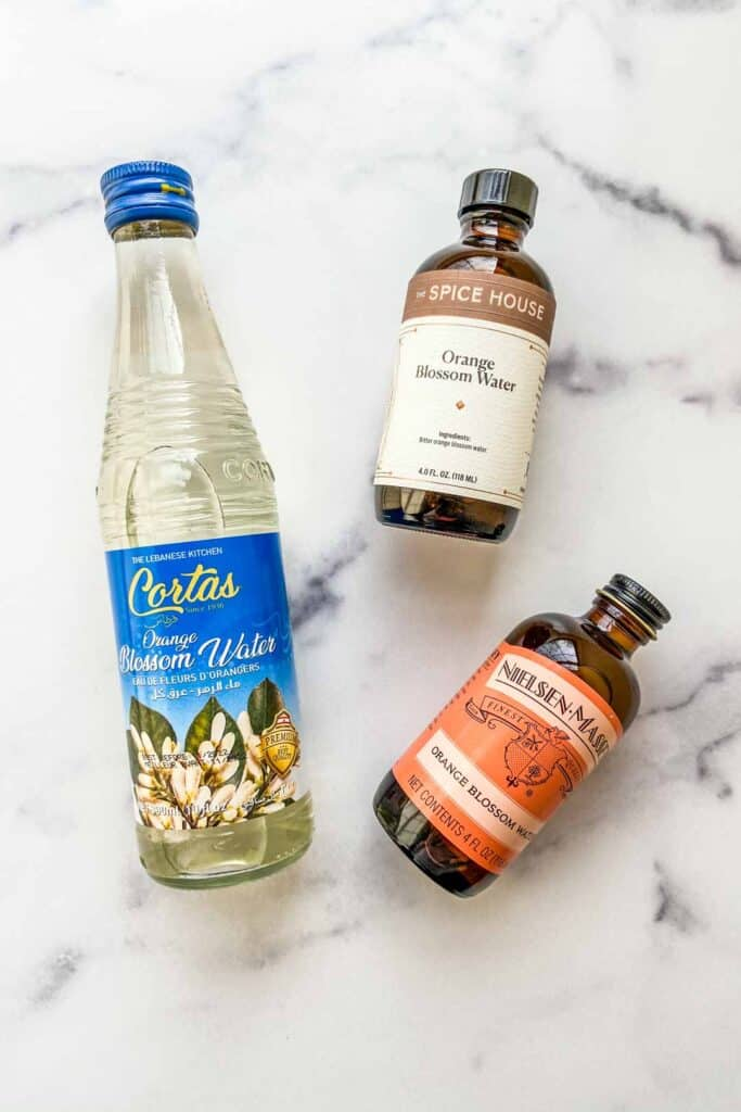 Three bottles of orange blossom water on a marble background.