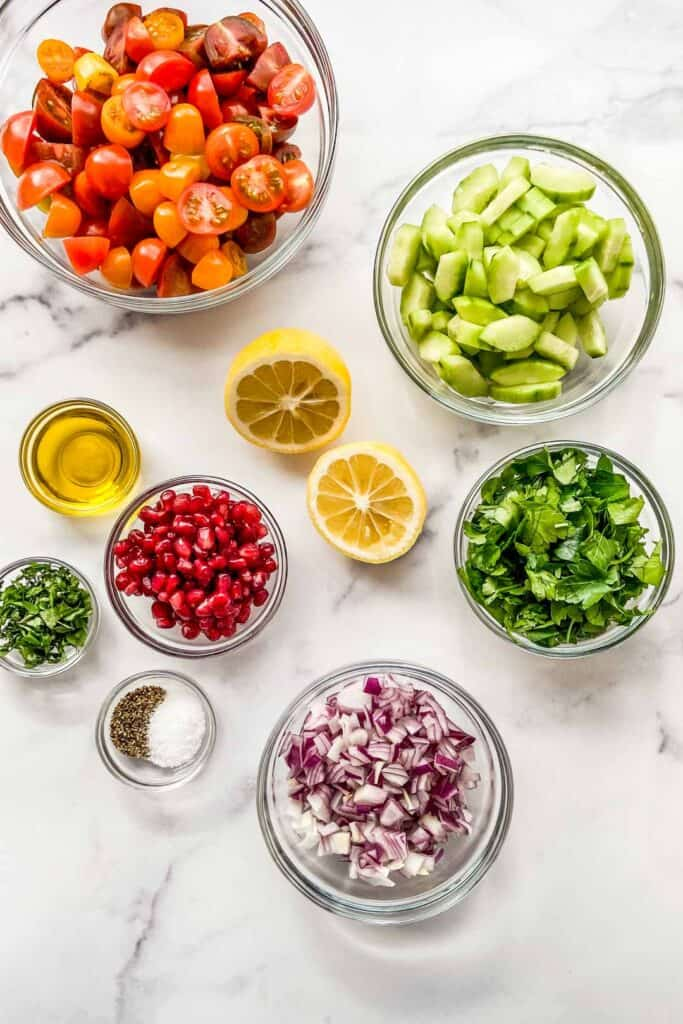 Middle Eastern salad ingredients in small bowls on a marble background.
