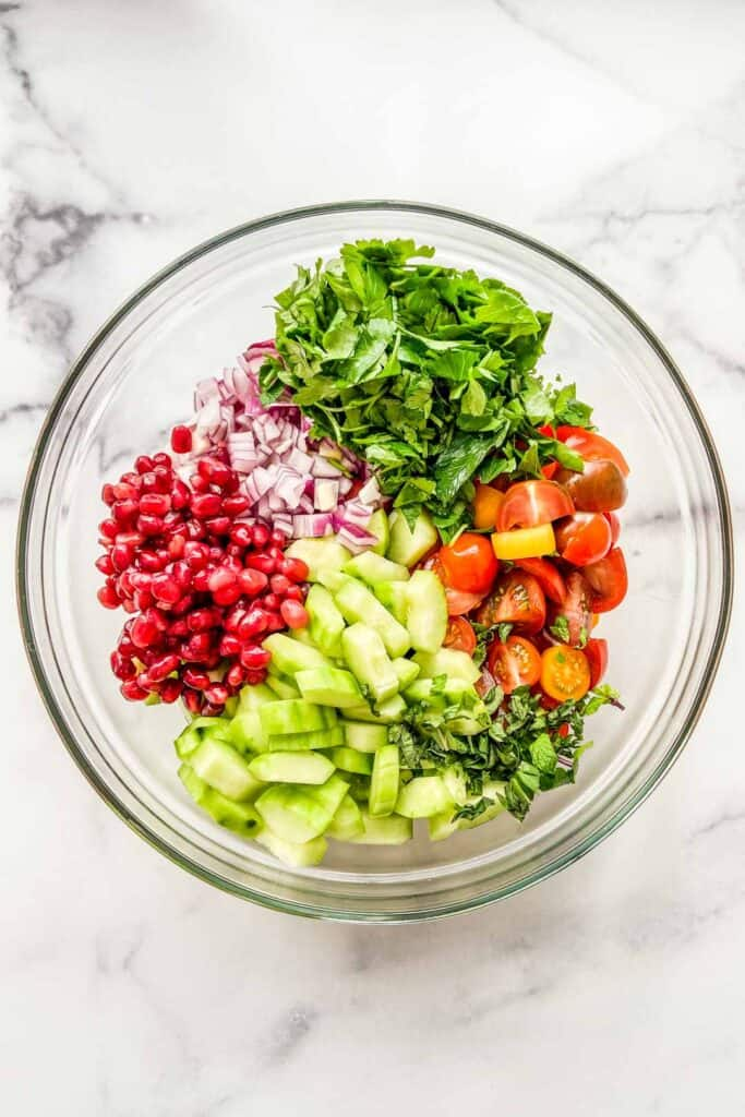 Ingredients for a cucumber tomato chopped salad in a mixing bowl.