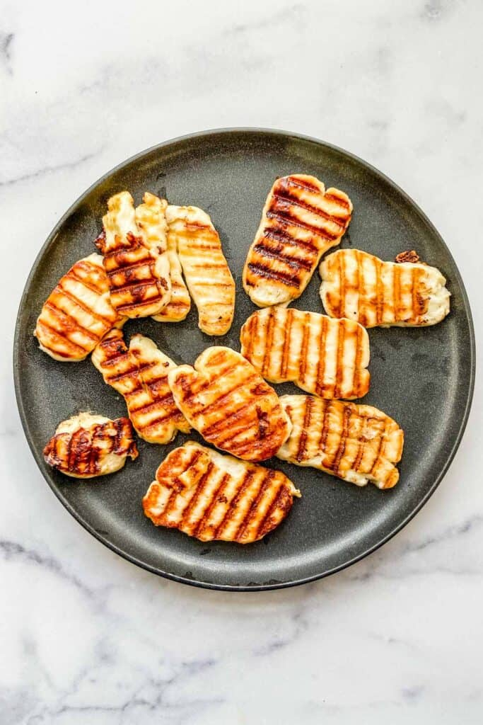 Several pieces of grilled halloumi cheese on a black plate.