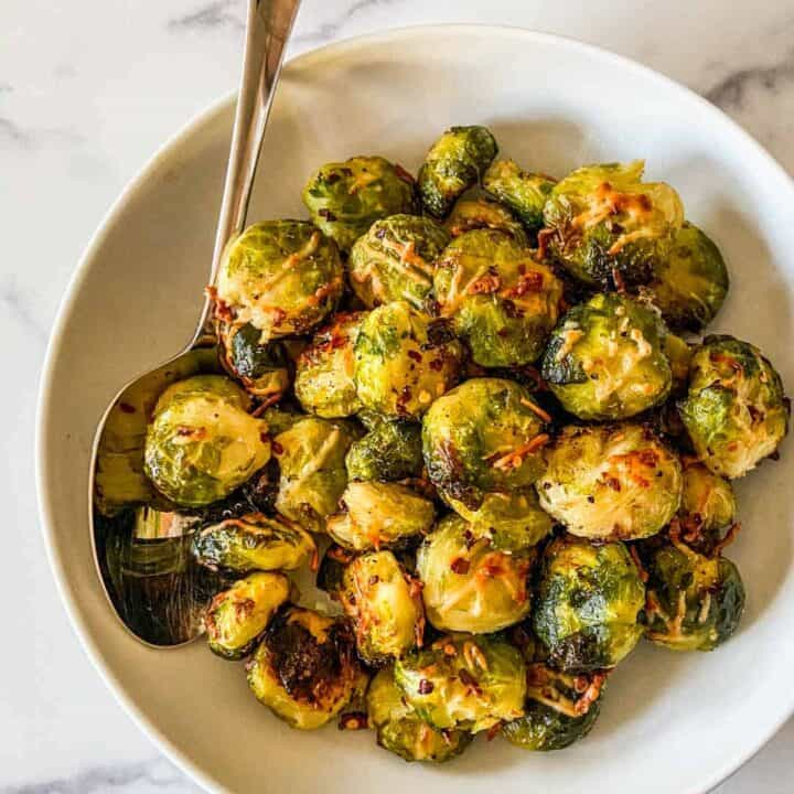 Smashed Brussels sprouts in a serving bowl with a large spoon.