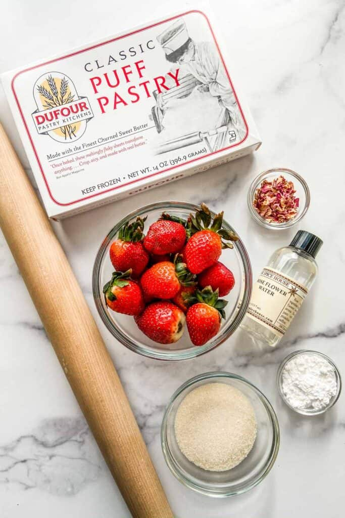 Ingredients for strawberry tartlets alongside a rolling pin.