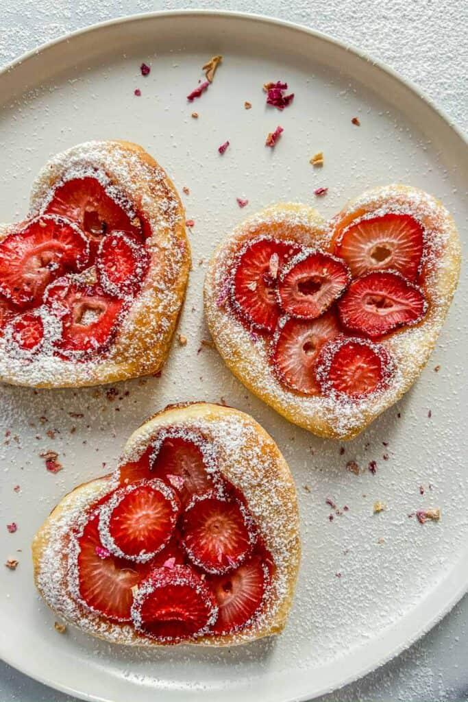 Three strawberry tarts on a white plate.