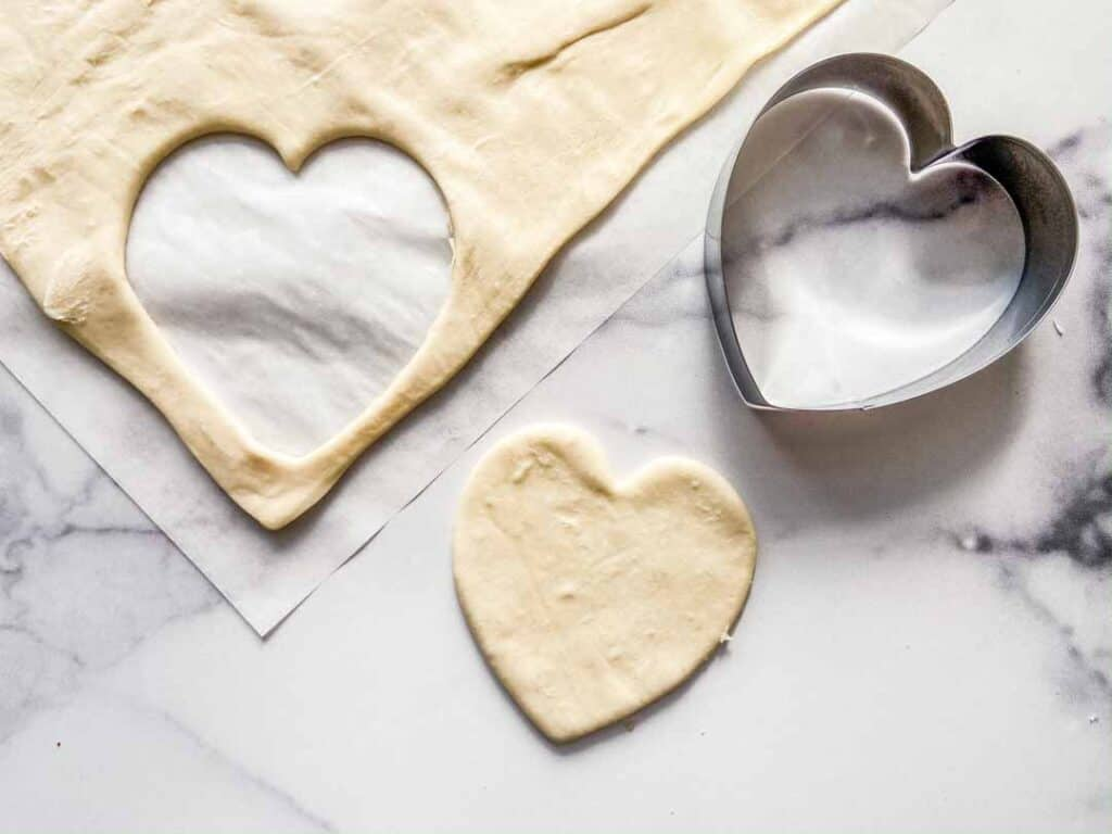 Cutting hearts from the puff pastry dough.