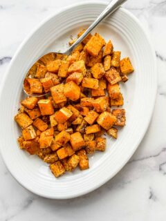Butternut squash topped with za'atar on a serving plate.