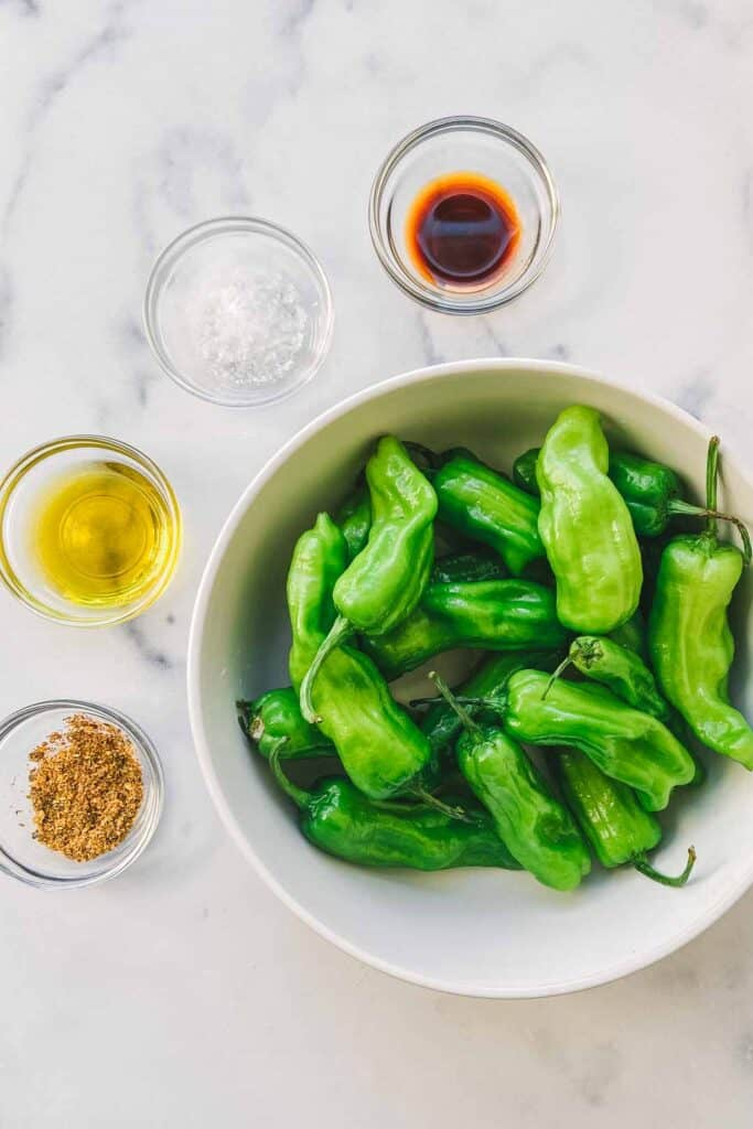 A bowl of shishito peppers next to small glass bowls of togarashi seasoning, sea salt, olive oil, and soy sauce.