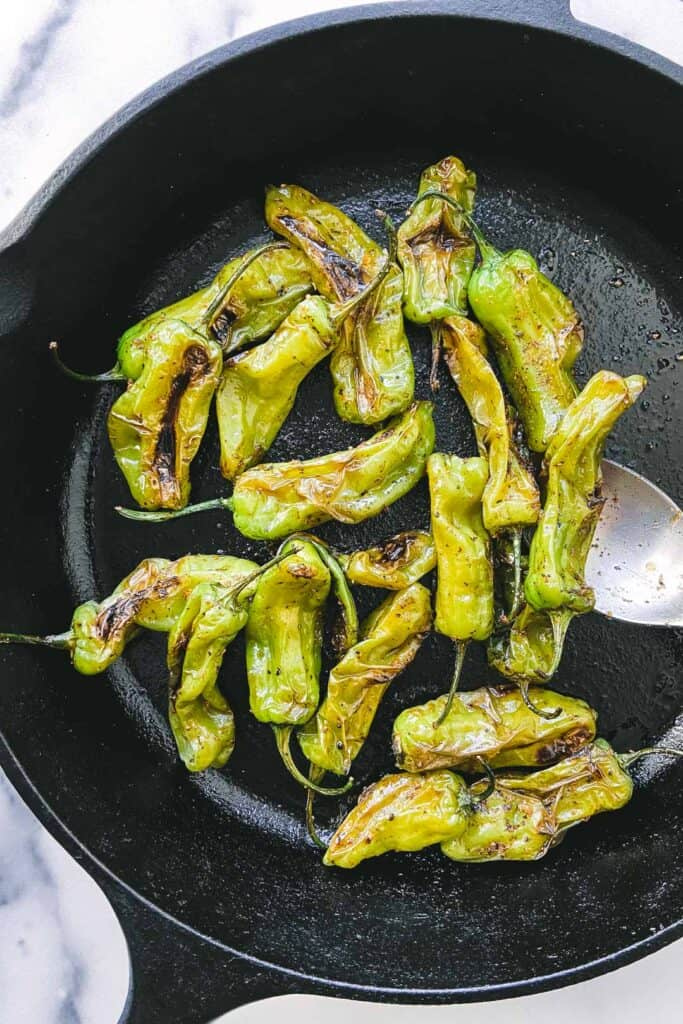 Shishito peppers in a cast iron skillet.