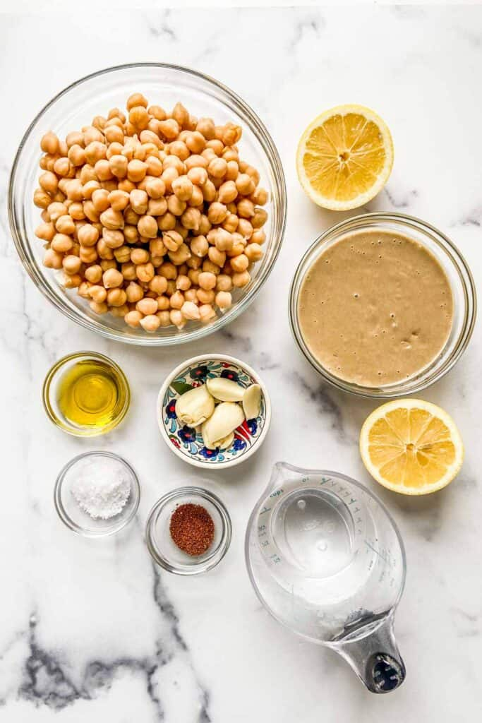 Bowls of chickpeas, tahini, olive oil, sumac, and garlic next to a measuring cup of water and a halved lemon.