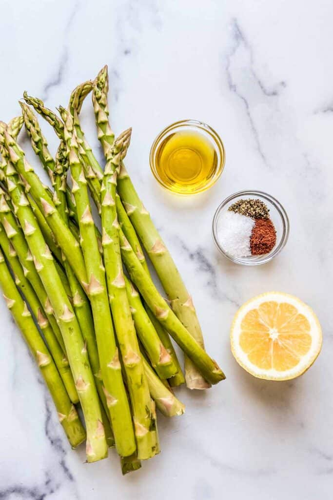 A bunch of asparagus, a small bowl with salt and sumac, half a lemon, and a small bowl of olive oil.