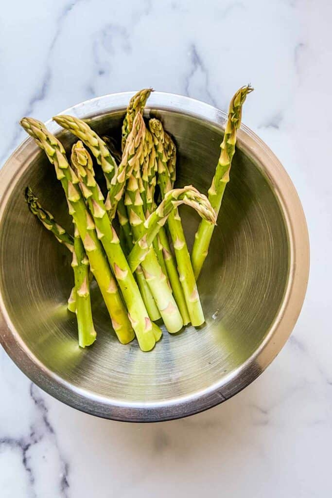 A large metal bowl with a bunch of asparagus.