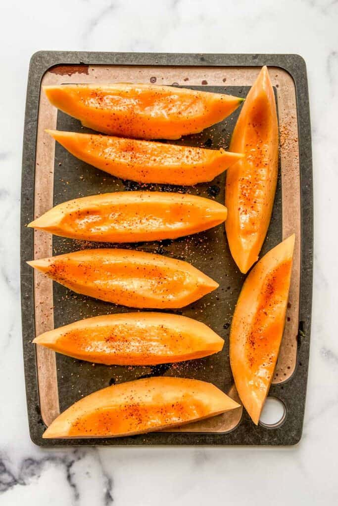 Slices of cantaloupe on a black cutting board.