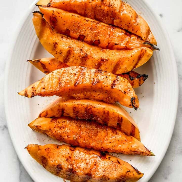 Grilled cantaloupe on a white serving plate.