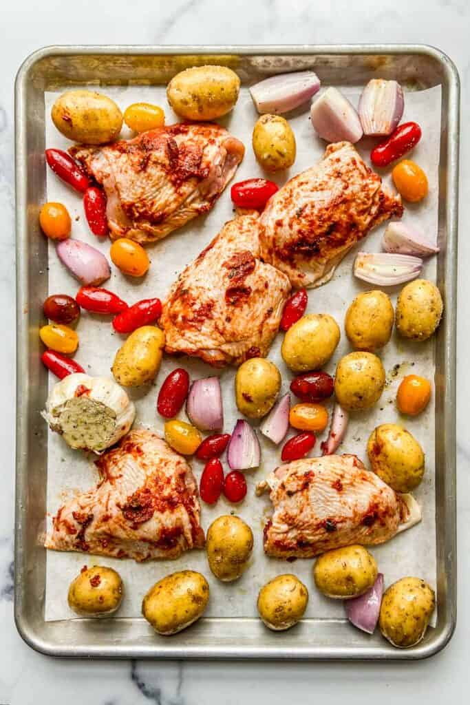 A sheet pan with uncooked chicken, potatoes, and tomatoes.