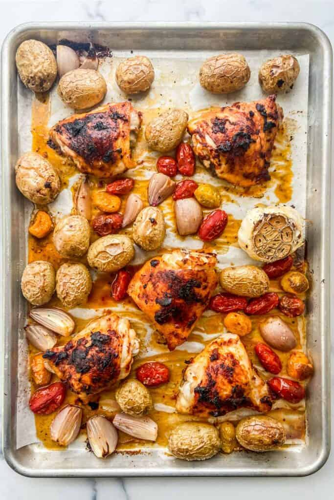A sheet pan with roasted chicken, potatoes, tomatoes, and a head of garlic.