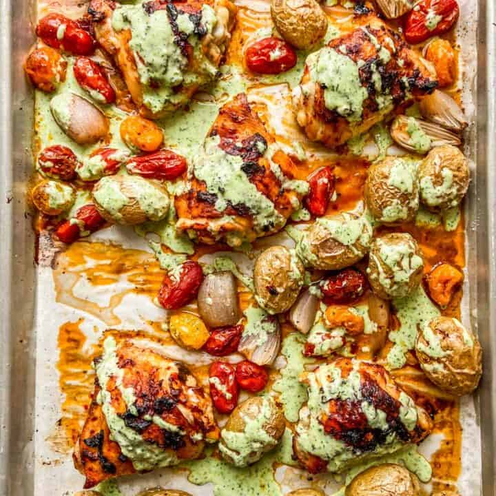 A sheet pan with roasted chicken, potatoes, tomatoes, and drizzled with a garlic yogurt sauce.