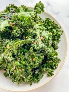 A bowl of kale chips sitting on a marble background.