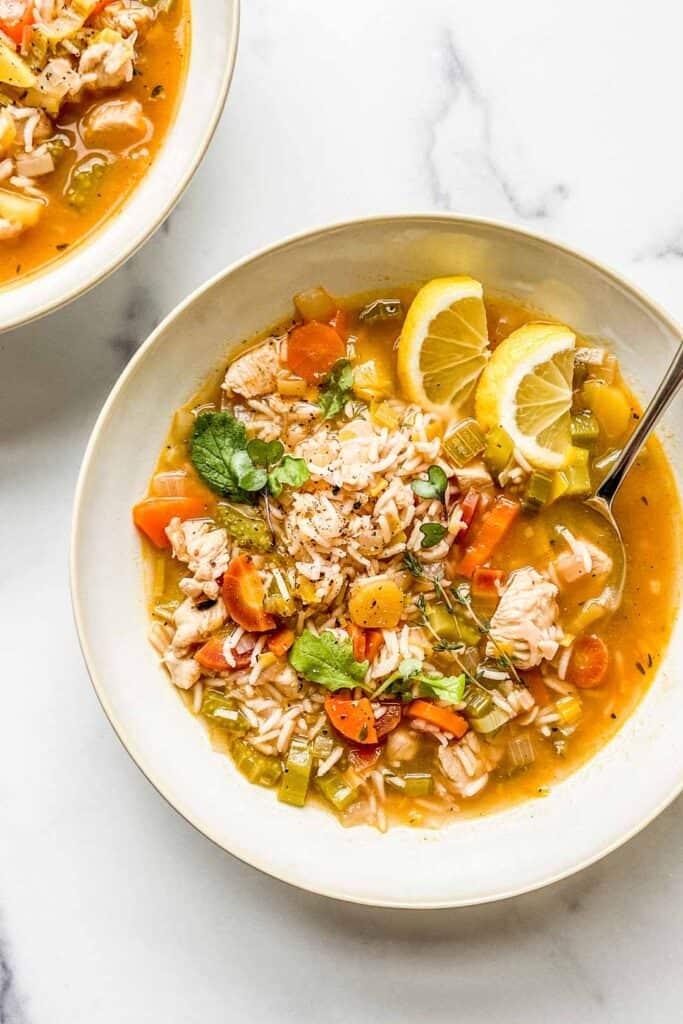 A closeup shot of a bowl of lemon chicken rice soup.