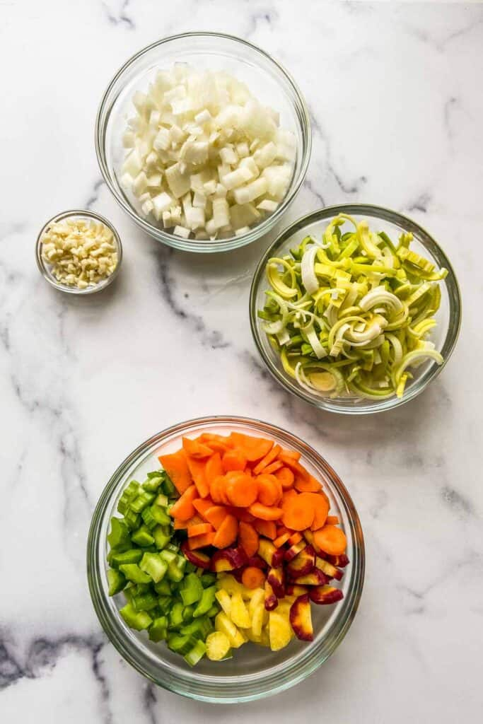 Four bowls of chopped vegetables - including onion, leeks, garlic, carrots, and cucumber.