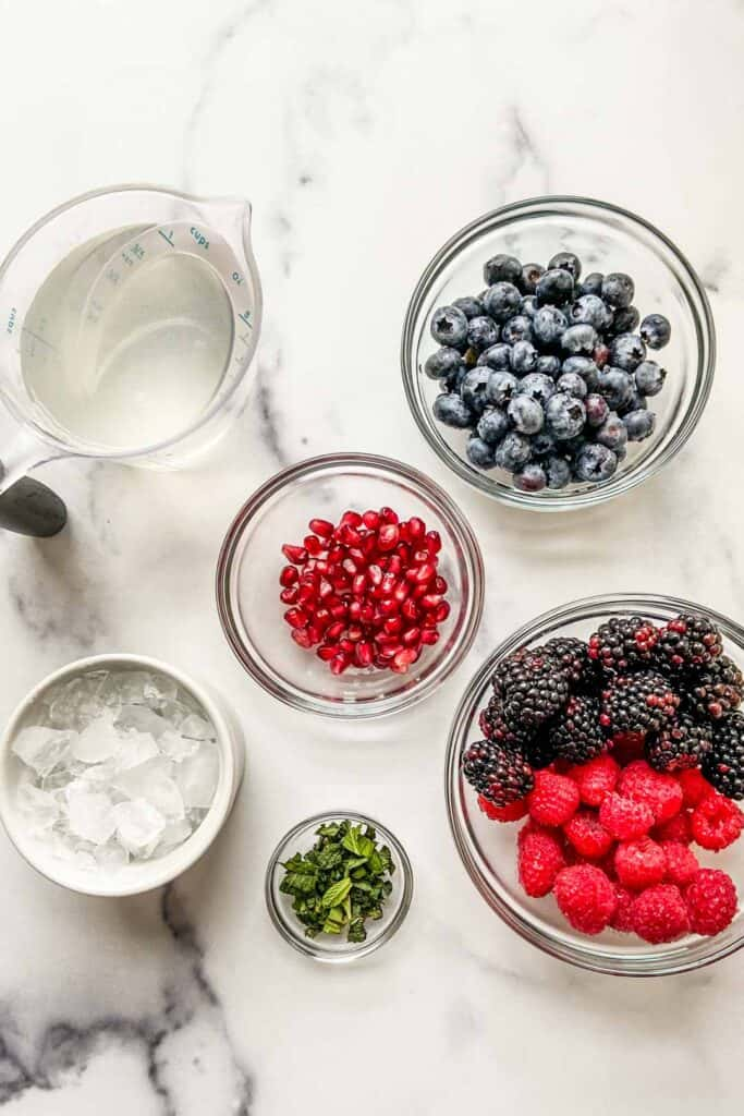Ingredients for nature's cereal (blueberries, pomegranate seeds, raspberries, blackberries, mint, coconut water, and ice) on a marble background.