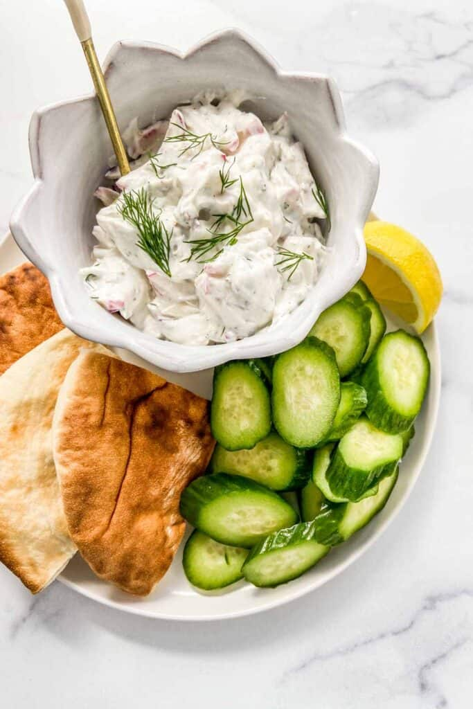 A bowl of radish tzatziki on a plate with chopped cucumbers and sliced pita bread.