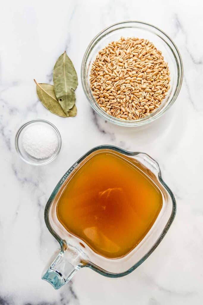 A measuring glass with vegetable stock, a bowl of farro, two bay leaves, and small bowl of kosher salt on a marble background.