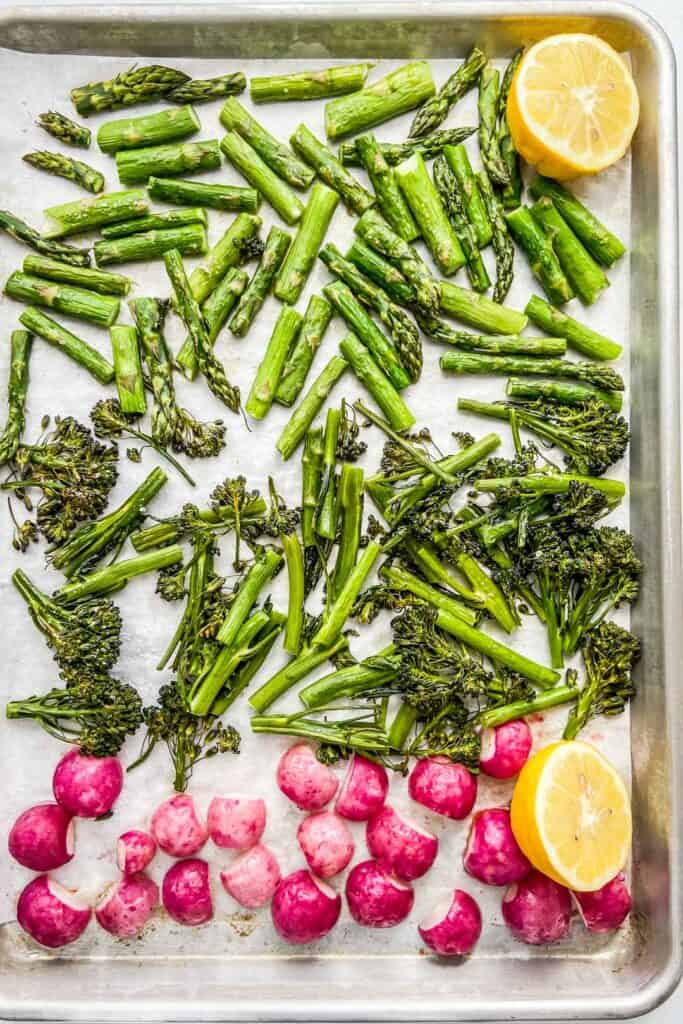 A sheet pan with roasted asparagus, broccolini, and radishes.