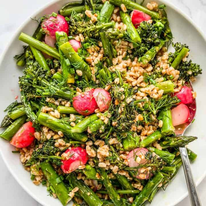Roasted vegetables with farro in a large white serving bowl with a silver serving spoon.
