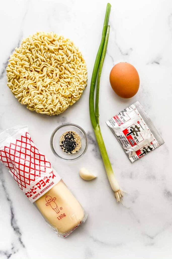 Ramen noodles, kewpie mayo, a green onion, an egg, a ramen spice packet, a clove of garlic, and a small bowl of sesame seeds on a marble background.