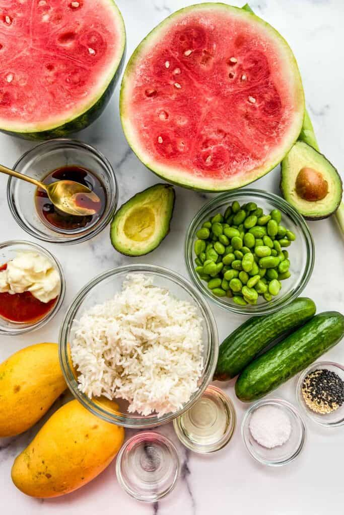 A halved watermelon, halved avocado, bowl of rice, bowl of edamame, green onion, cucumbers, mangoes, a bowl of marinating sauce, a bowl of sriracha mayo, and a bowl of sesame seeds on a marble background.