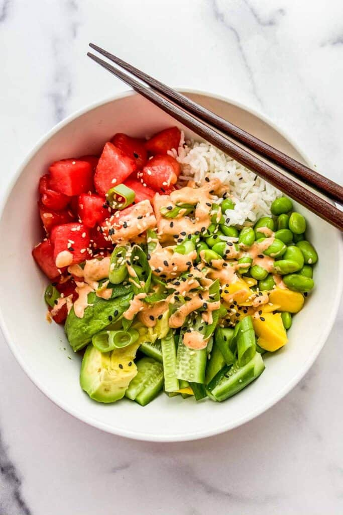 An overhead shot of a bowl of watermelon poke with chopsticks resting on the bowl.