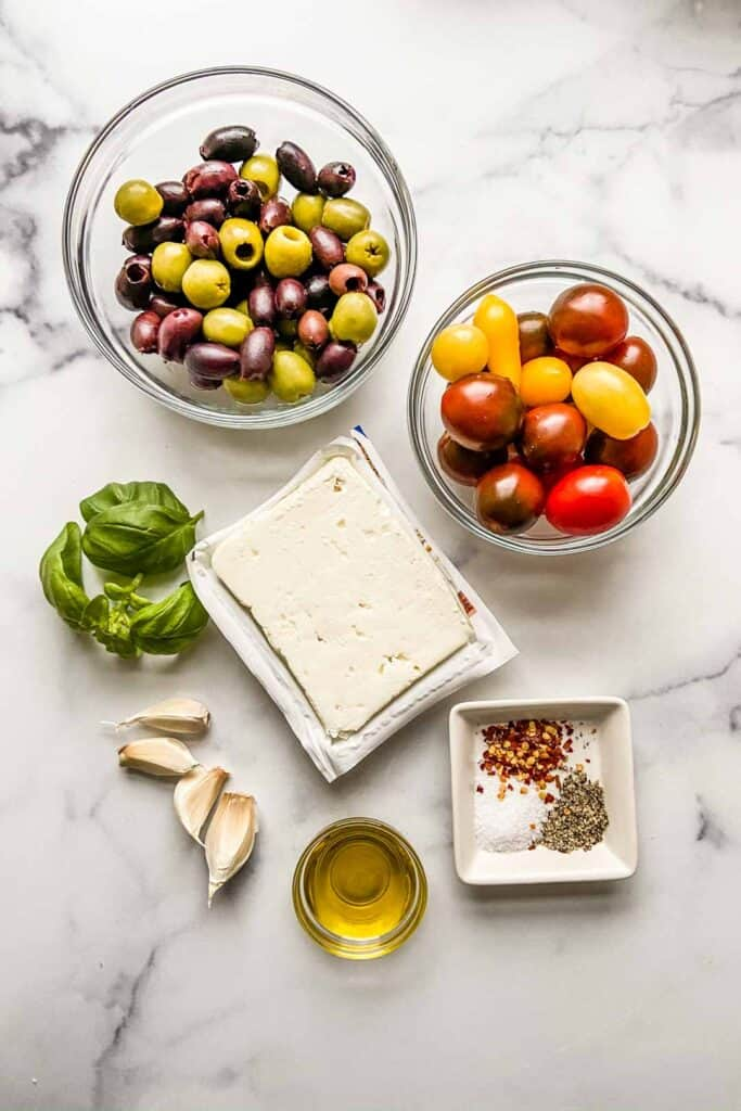 A bowl of olives, a bowl of cherry tomatoes, a block of feta, four garlic cloves, some basil leaves, a small bowl of olive oil, and some salt, pepper, and red pepper flakes.