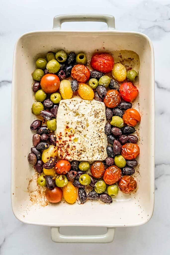 A baking dish with a block of feta, olives, and tomatoes.